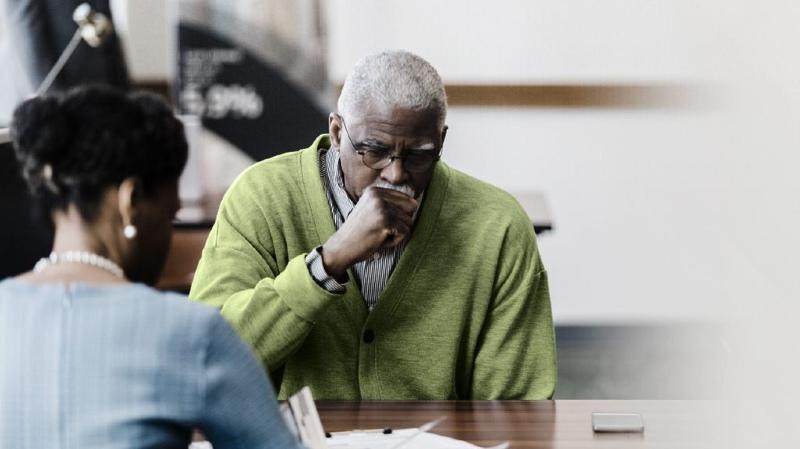 Một người đàn ông mặc áo liền quần màu xanh lá cây và ho vì anh ta có thể có các triệu chứng của ung thư phổi giai đoạn 1.
